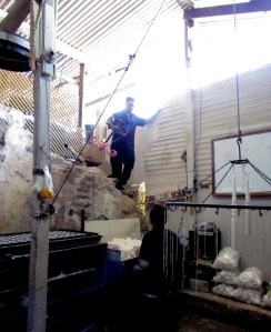 A worker climbs down from the supply area in the back of the candle shop. I believe that is part of the ruins jutting out!