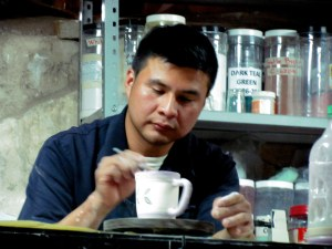 A potter decorates a mug at the back of the candle shop