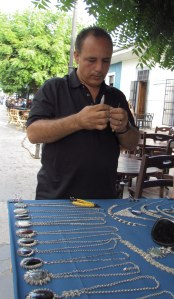 An artist adjusts a link before selling Gerda his hand-twisted silver necklace