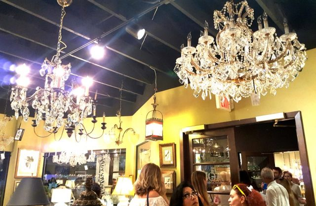 The woman, below, looks up at a gorgeous chandelier rescued from an estate sale in River Oaks!